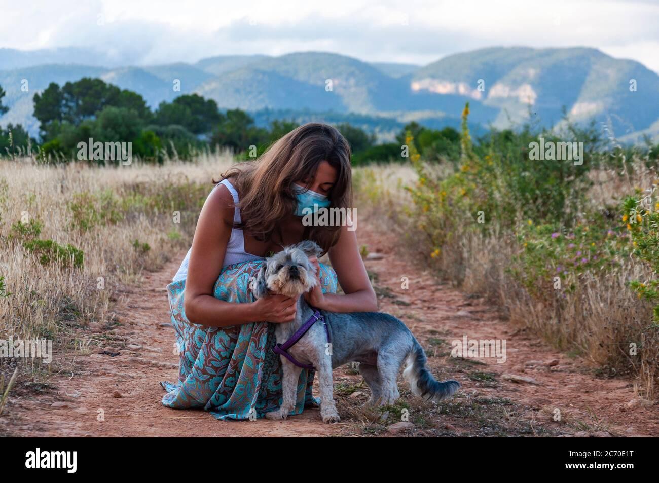 Junge Frau mit einer Gesichtsmaske Überprüfung und Pflege ihres Hundes Stockfoto
