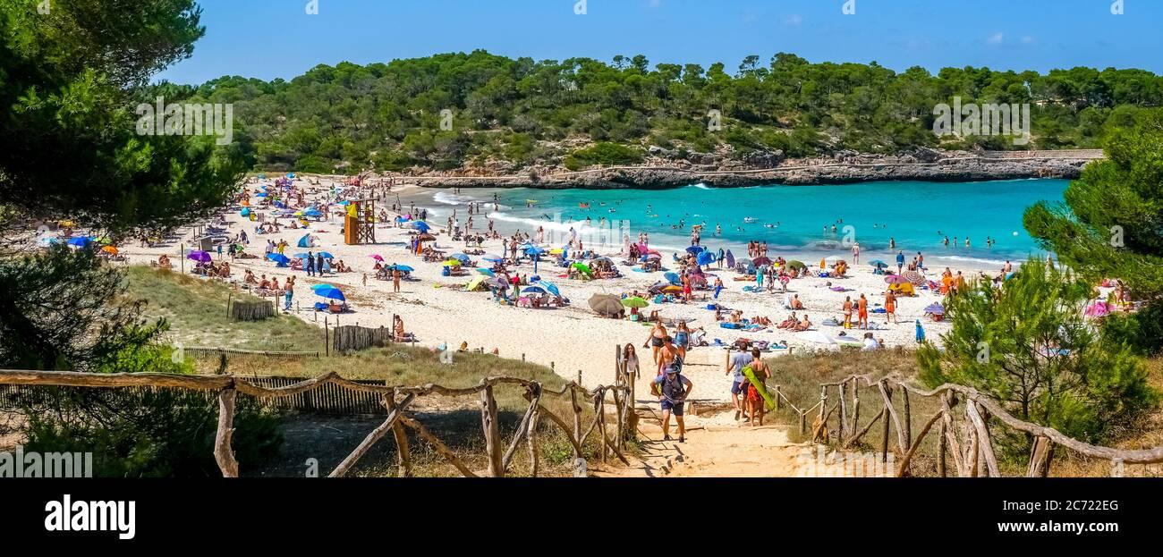 Einsamer Strand im Parc Natural de Mondrago und Strand S'amador mit zahlreichen Badegäste, die in der Regel halten den Mindestabstand während der Corona pandemi Stockfoto