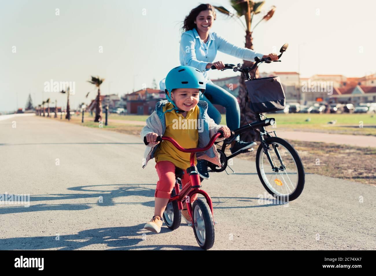 Kleines Kind, das mit seiner Mutter auf einem Fahrrad in einem Stadtpark ein Laufrad fährt Stockfoto