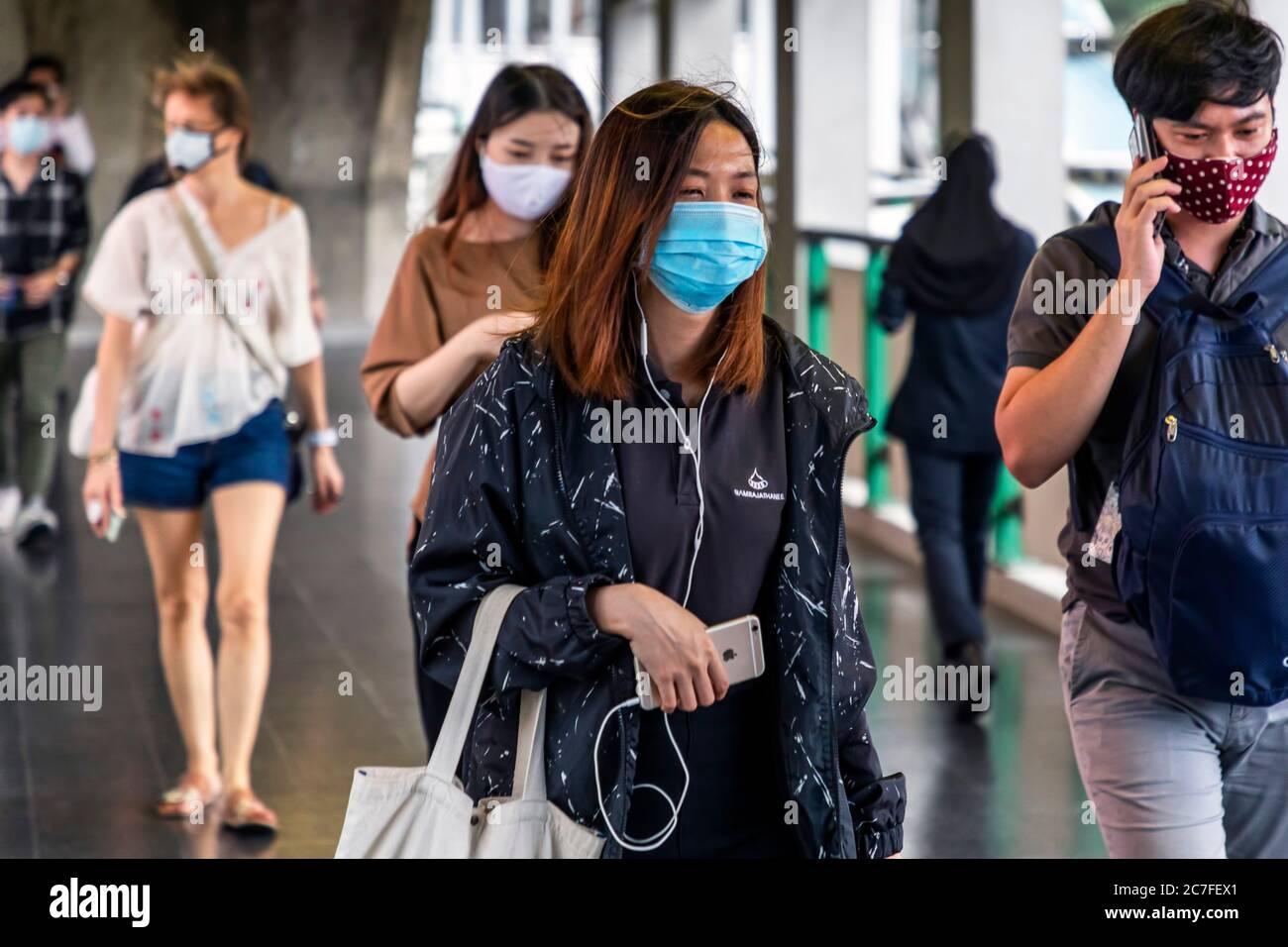 Fußgänger tragen Gesichtsmaske mit Handy während covid 19 Pandemie, Bangkok, Thailand Stockfoto