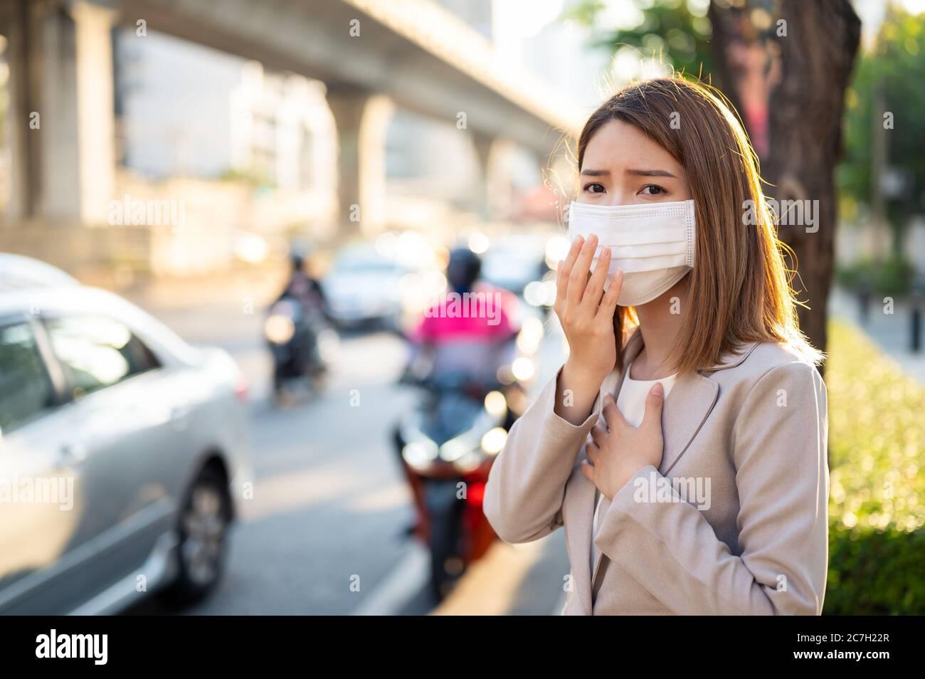 Junge Geschäftsfrau trägt chirurgische Maske und hugen beim Gehen in der Öffentlichkeit in Coronavirus oder COVID-19 Verbreitung Situation Stockfoto