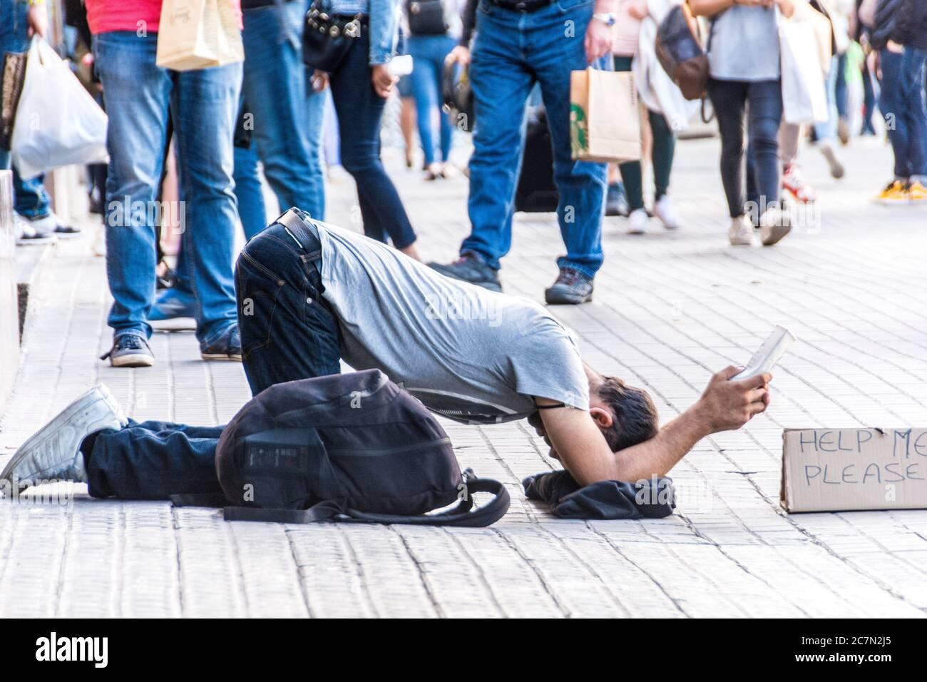 Ein obdachloser junger Mann mit einem Rückzieher mit einem Schild, das besagt: 'Hilf mir bitte', Barcelona, Spanien. Stockfoto