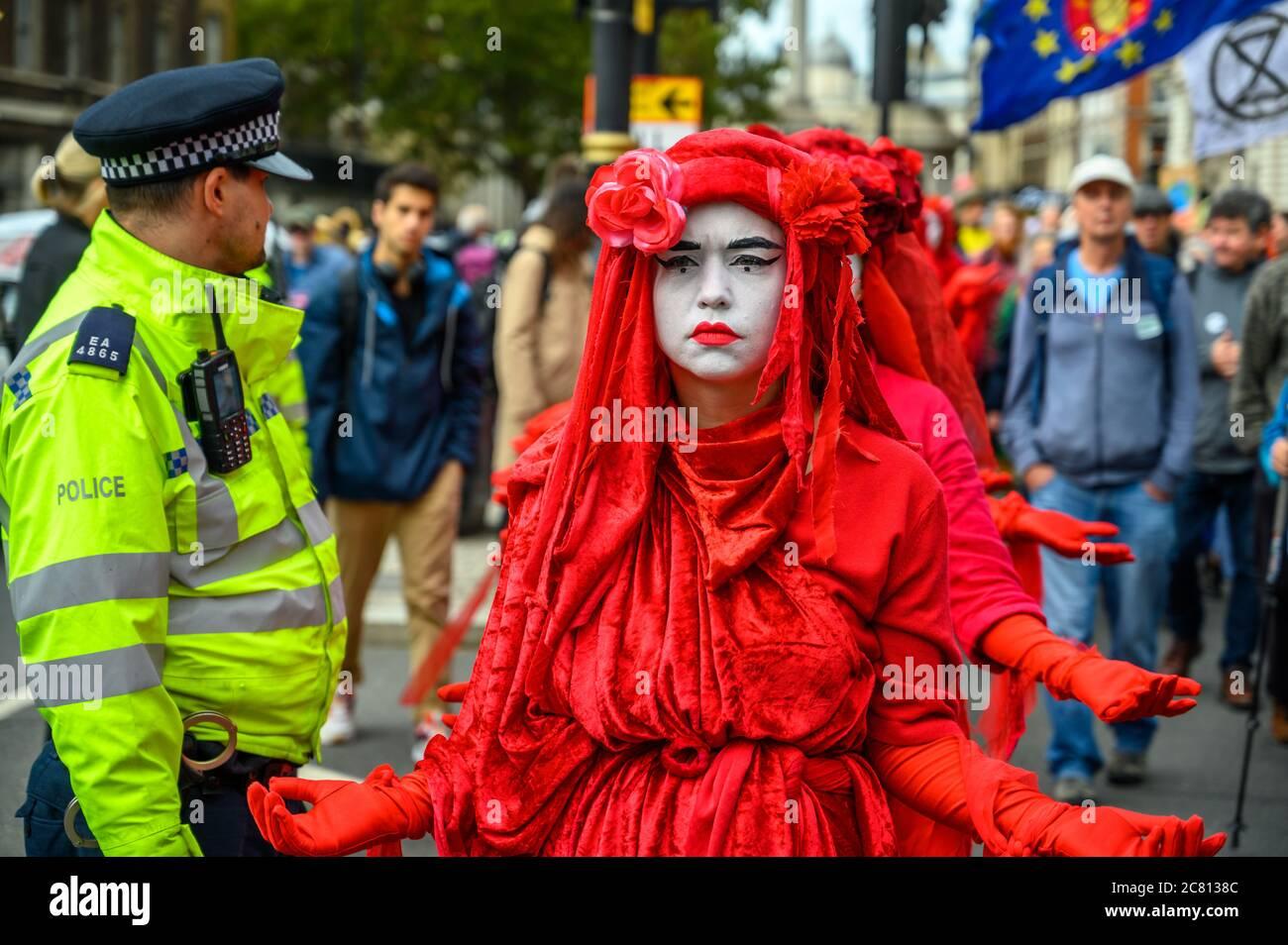 LONDON - 18. OKTOBER 2019: Nahaufnahme der Rebellion der Roten Brigade Demonstranten, die an einem Metropolitan Police Officer vorbeigingen Stockfoto