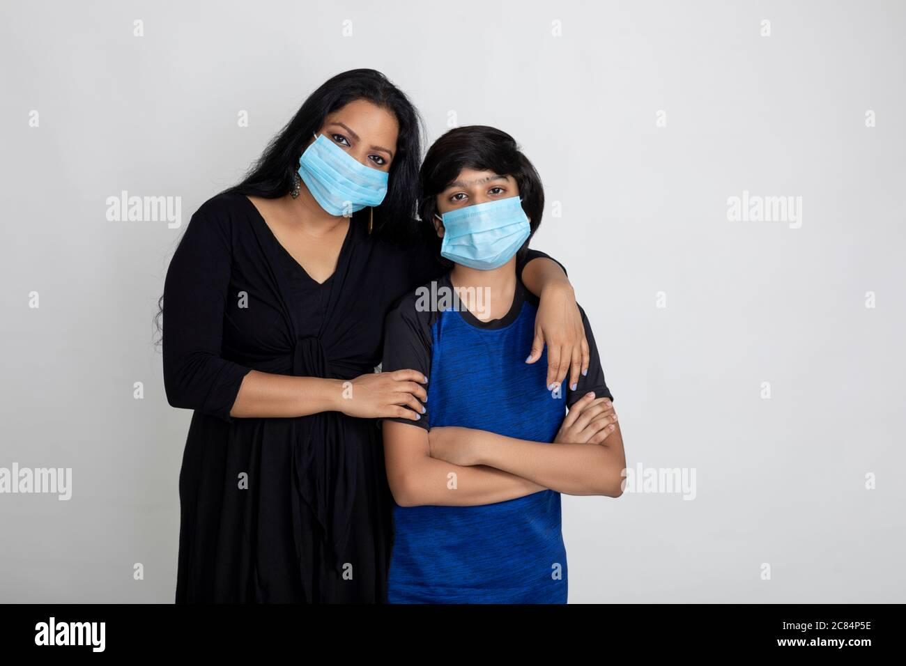 Indische Mutter und Sohn tragen Covid Schutzmaske, Frau und kleiner Junge stehen zusammen mit Gesichtsmaske Stockfoto