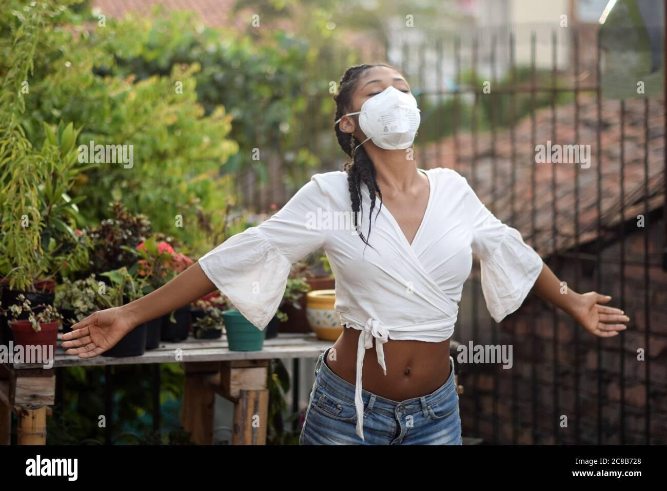 Junge schwarze Frau in Gesichtsmaske öffnet ihre Arme und entspannt im Balkon Stockfoto