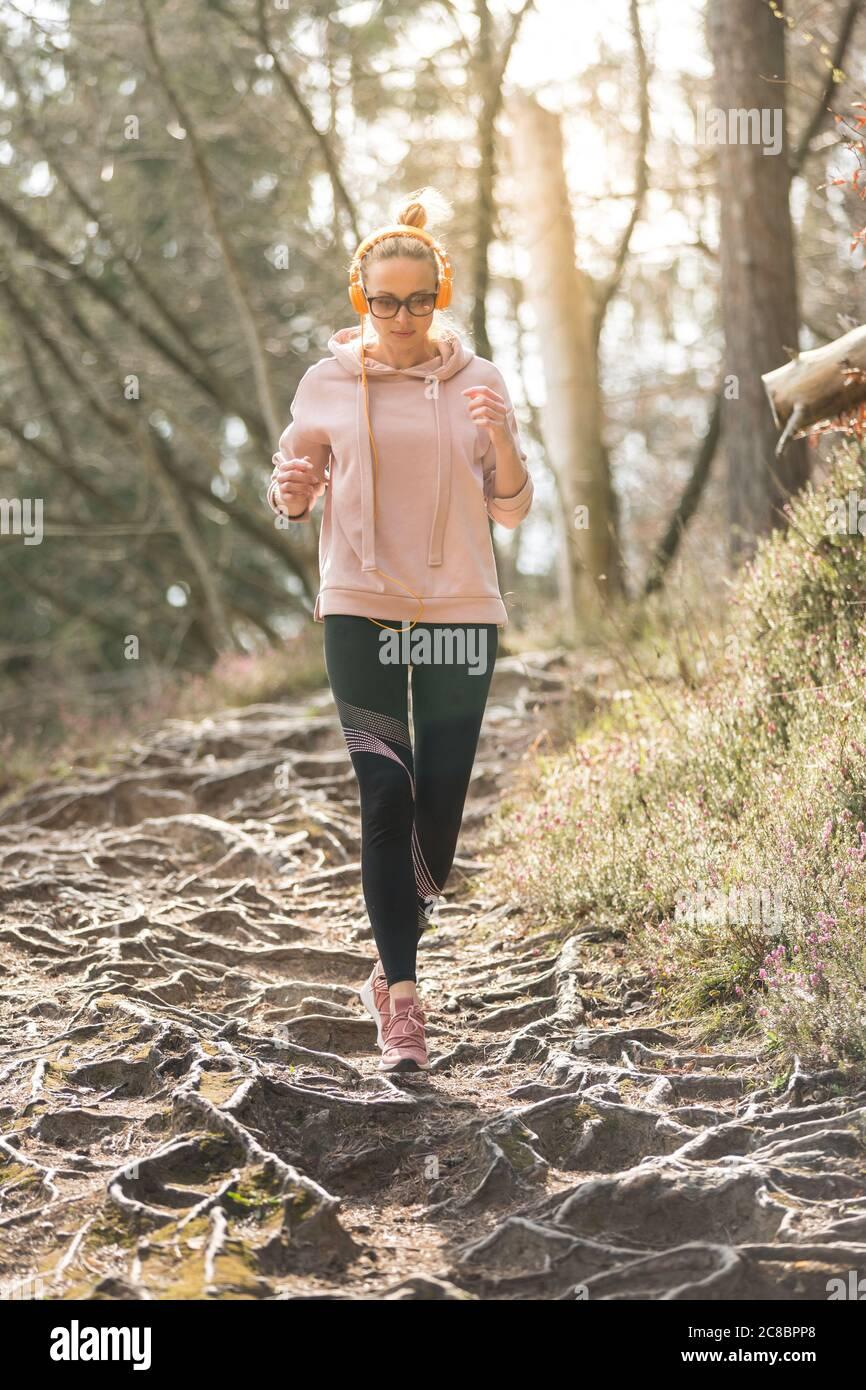 Aktive sportliche Frau, die während des Laufs im Herbstwald Musik hört. Laufbeine trainieren im Freien. Gesundes Lebensgefühl junger Menschen Stockfoto