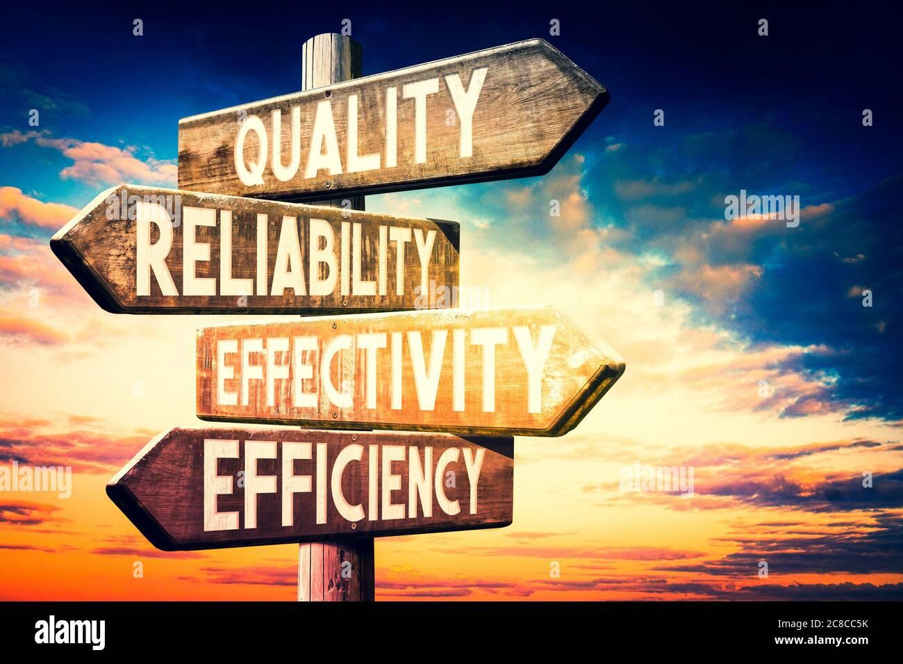 Qualität, Zuverlässigkeit, Effektivität, Effizienz - Holzschild, Wegweiser mit vier Pfeilen Stockfoto