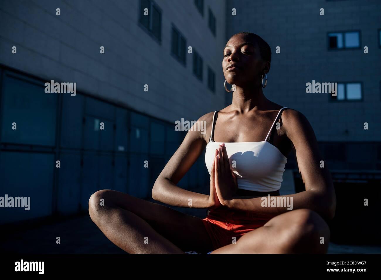 Junge Frau mit geschlossenen Augen meditiert, während sie gegen Gebäude sitzt In der Stadt Stockfoto