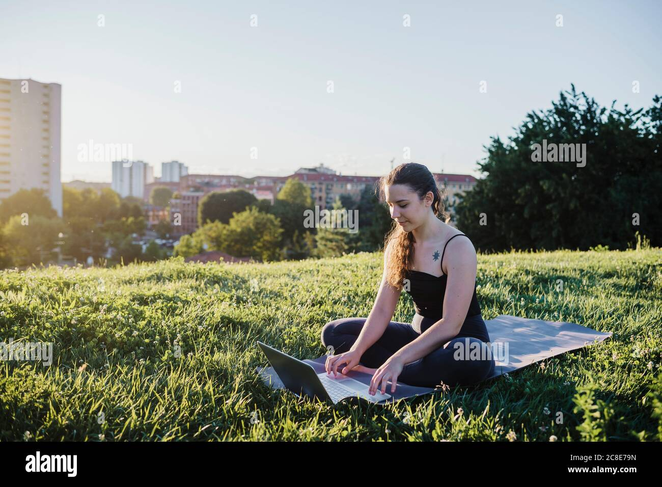 Sportliche junge Frau mit Laptop, während sie auf der Trainingsmatte sitzt Im Stadtpark Stockfoto