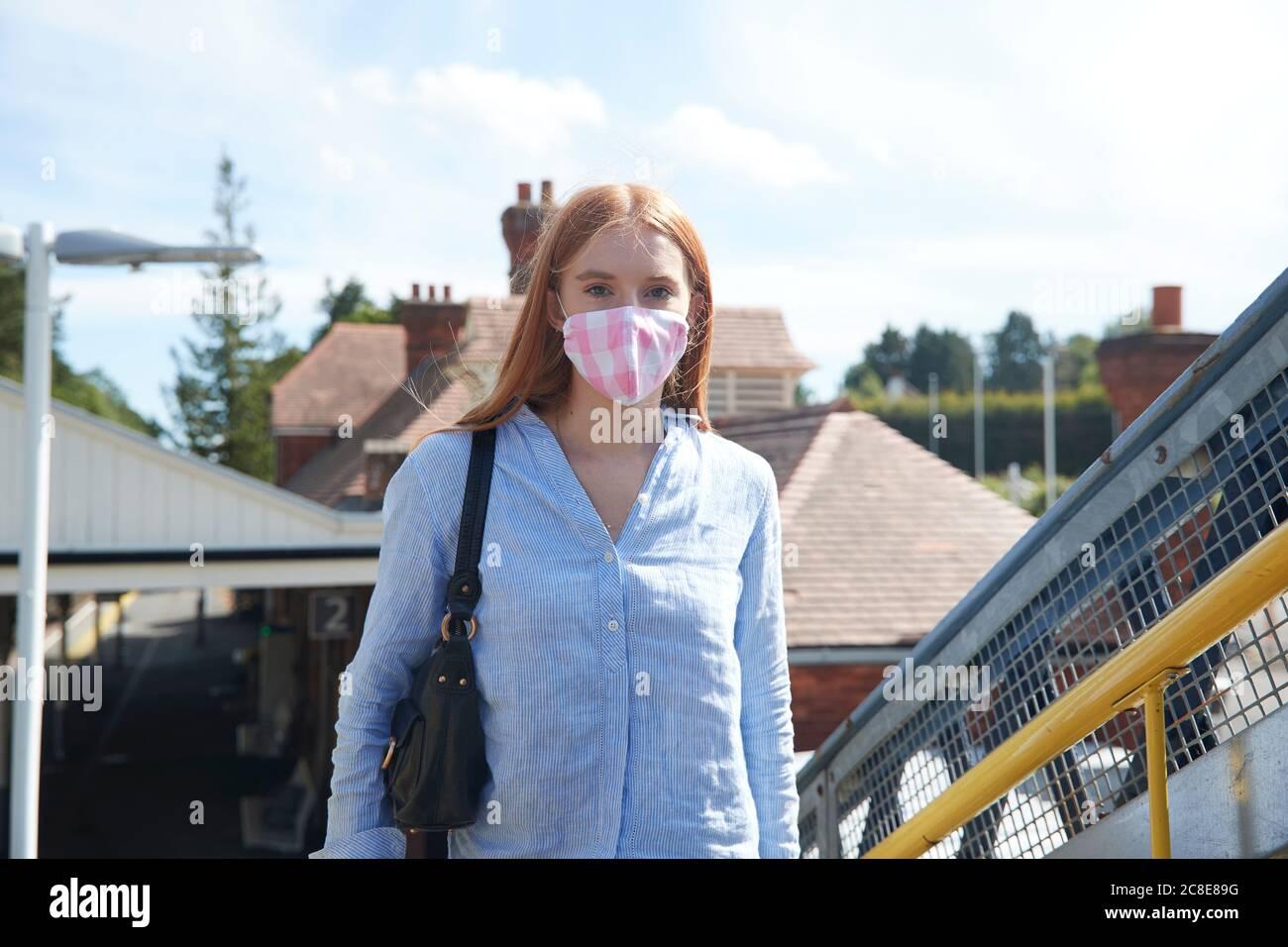 Junge Frau mit Schutzmaske am Bahnhof Stockfoto