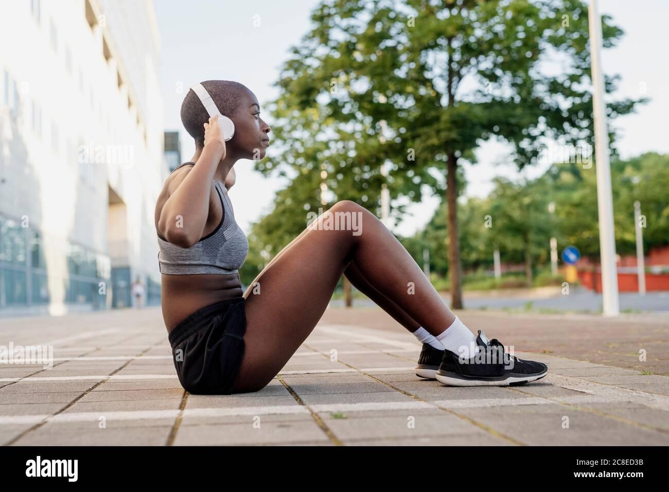 Junge Frau, die Musik hört, während sie auf dem Fußweg in der Stadt trainiert Stockfoto