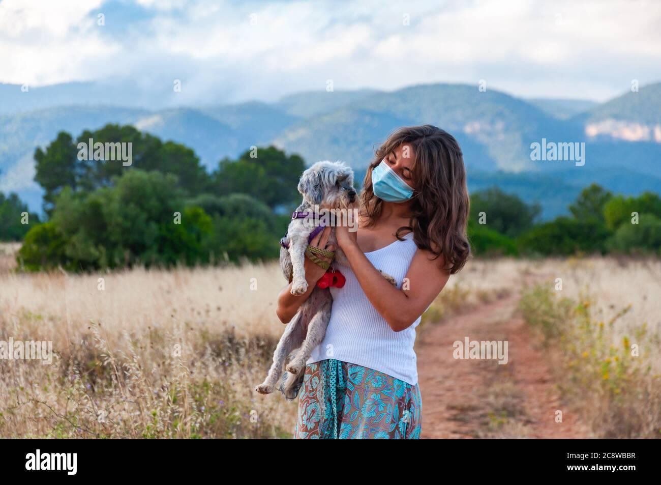 Junge Frau mit einer Gesichtsmaske, die ihren Hund ansieht Stockfoto