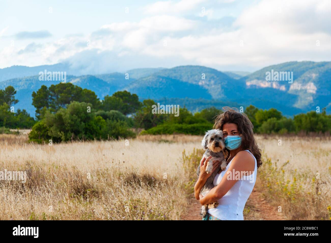Junge Frau mit Gesichtsmaske in Begleitung ihres Hundes im Wald Stockfoto