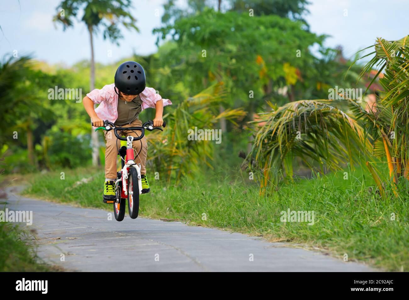Radfahren auf dem Land. Junge Fahrer Kind in Helm und Sonnenbrille Fahrrad fahren. Glückliches Kind hat Spaß auf leeren Trail. Aktiver Familienleben, Sport, o Stockfoto