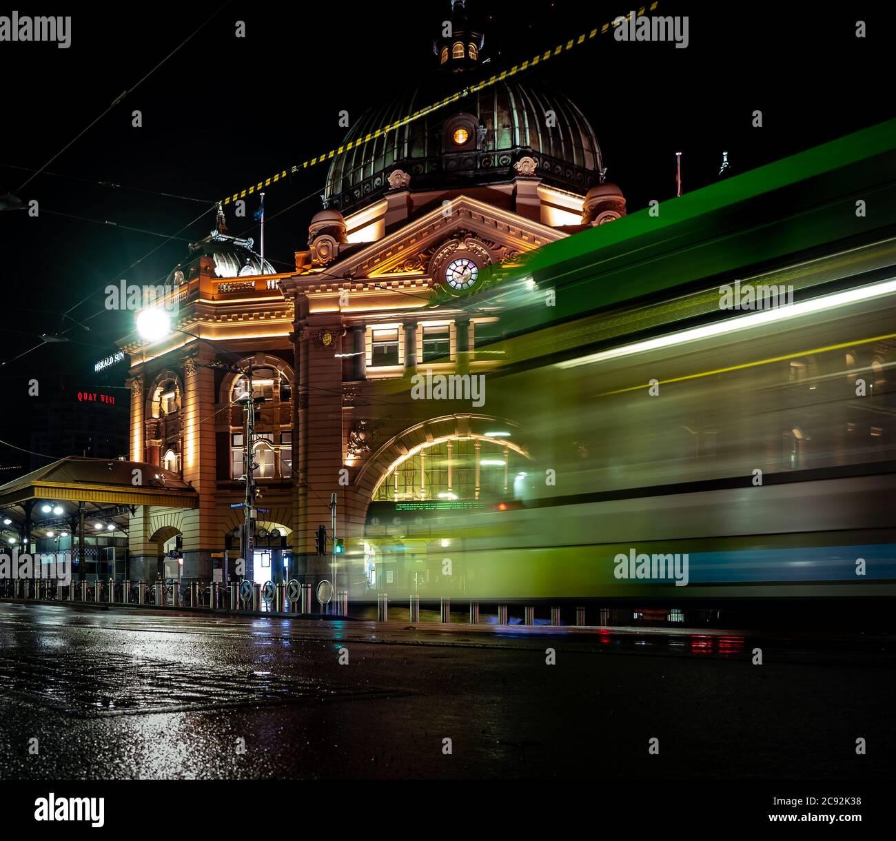 Straßenbahnen und Autos vor der berühmten melbourne Flinders Street Station sind von Lichtern durchleuchtet Stockfoto