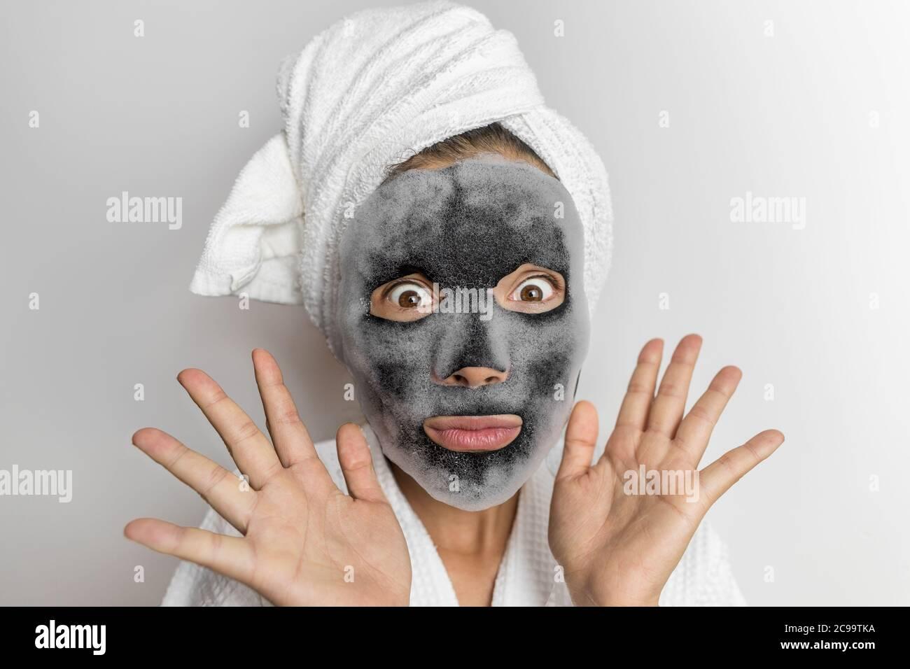 Gesichtsmaske Blase Schaum Gesichtsbehandlung lustige Frau in Beauty-Spa suchen schockiert oder überrascht, gruselige Chemikalien in Beauty-Produkte. Asiatische Mädchen tragen Badetuch Stockfoto
