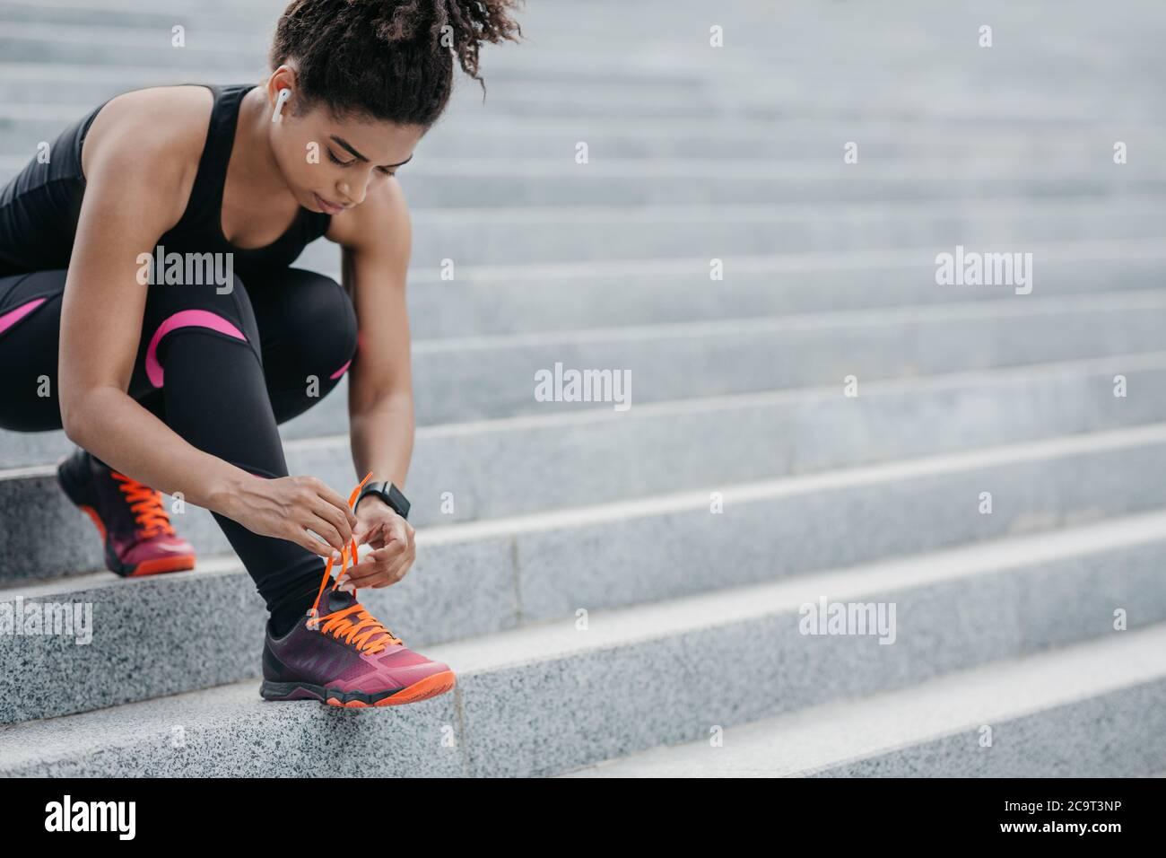 Läufer, die sich auf das Training vorbereiten. Afroamerikanische Mädchen mit kabellosen Kopfhörern und Fitness-Tracker binden Schnürsenkel auf Turnschuhe Stockfoto