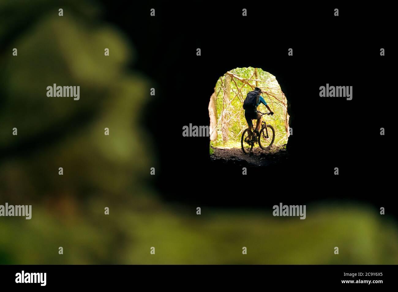 Radler mit Rucksack und Mountainbike am Ende eines Tunnels, Konzept von Sport und gesunder Lebensweise in der Natur, Kopierer Platz für Text Stockfoto