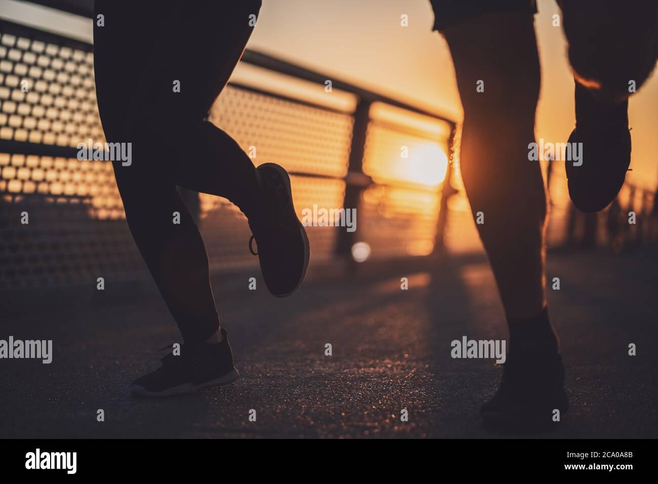 Körperteil Silhouetten von Paar, das in der Stadt im Sonnenuntergang joggt. Stockfoto