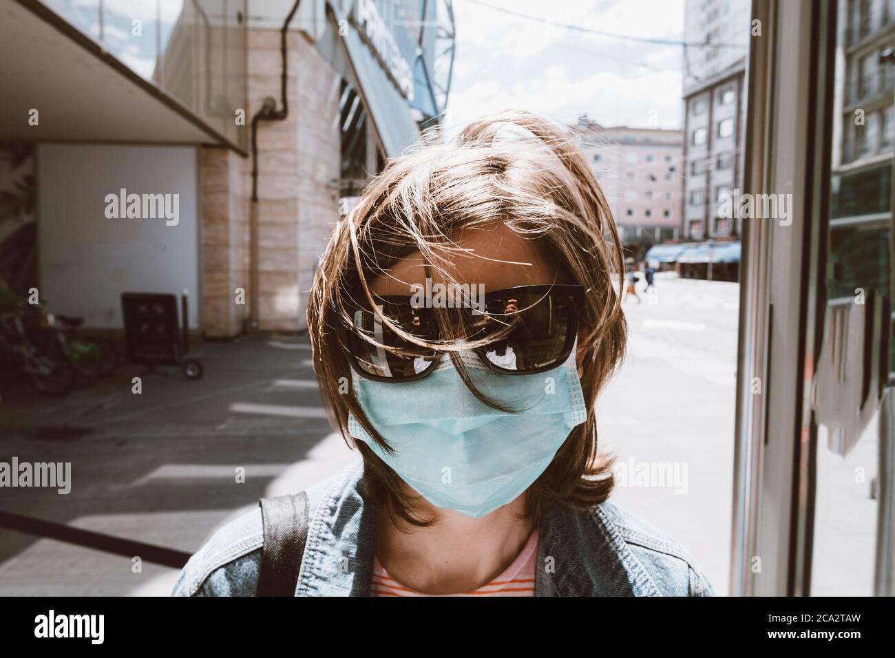 Frontansicht der Frau trägt Sonnenbrille und Atemschutzmaske in der leeren Stadt während COVID Coronavirus-Krankheit Pandemie Stockfoto