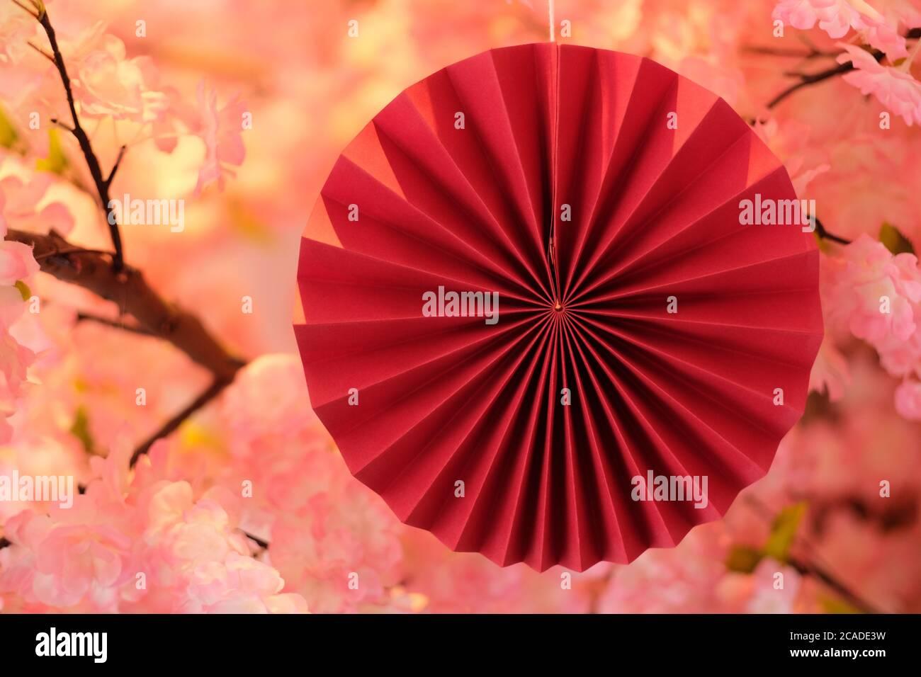 Nahaufnahme traditioneller japanischer Papierkunst (Origami) mit unscharfem rosa Sakura-Hintergrund. Japanisches Kulturkonzept Stockfoto