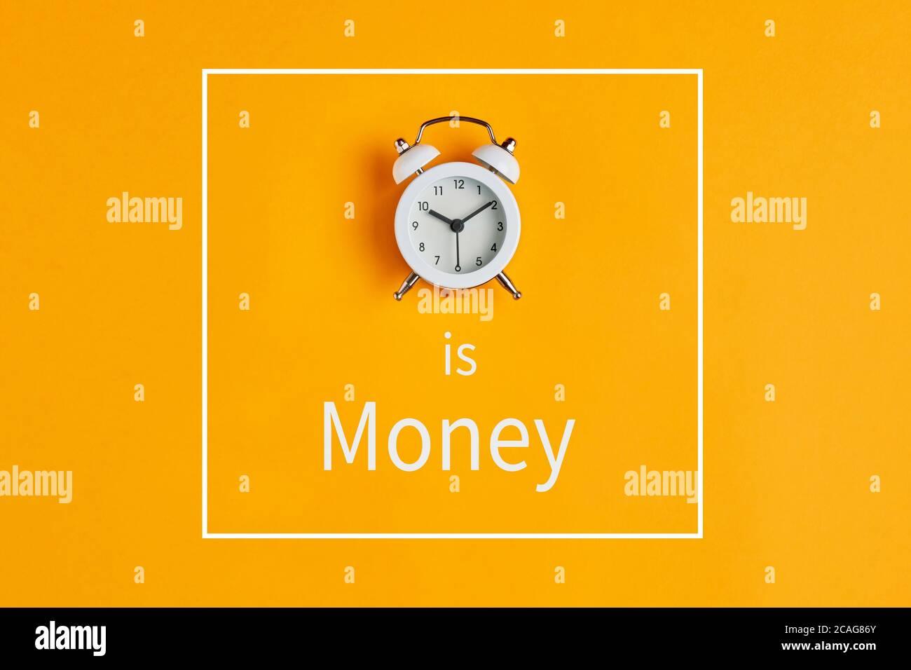 Zeit ist Geld Konzept mit Wecker und Text auf gelbem Hintergrund geschrieben. Wertvolle Ressource für das Ergebnis im Geschäft. Stockfoto
