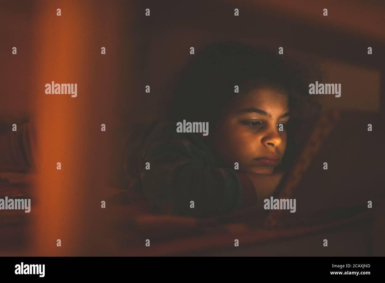 Kleines Mädchen im Alter von 8 Jahren ist mit ihrem digitalen Tablet in ihrem Bett. Sie wird nur von der Helligkeit des Bildschirms beleuchtet. Stockfoto