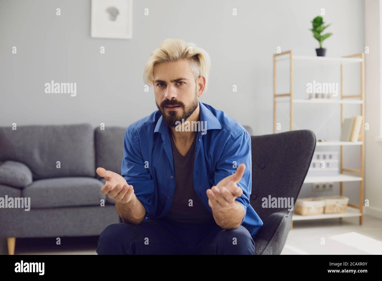 Verwirrt Hipster Mann sitzt im Sessel zu Hause Stockfoto