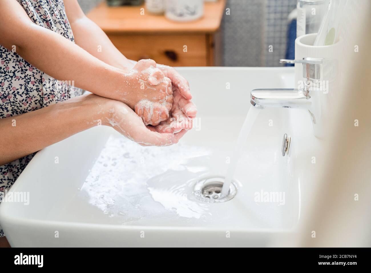 Mutter und Mädchen Kind waschen Hände zusammen im Waschbecken Mit viel Seife unter fließendem Wasser Stockfoto
