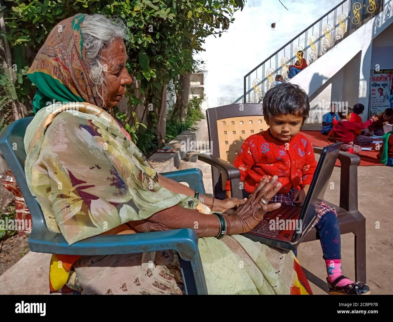 DISTRIKT KATNI, INDIEN - 13. JANUAR 2020: Eine alte Frau aus einem indischen Dorf, die einen Laptop mit kleinen Kindern im Freien betreibt. Stockfoto