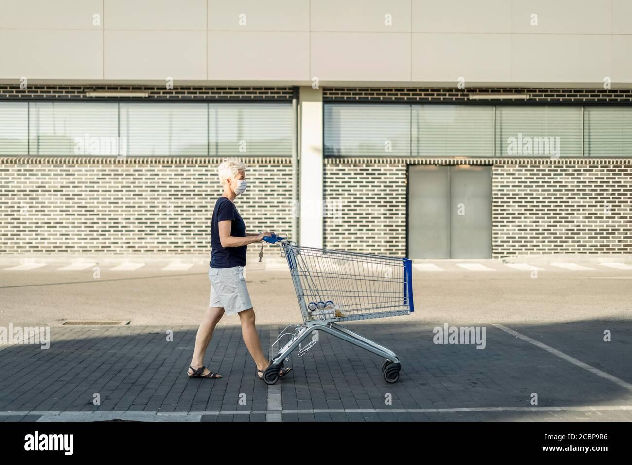 Frau in Schutzmaske mit Einkaufswagen vor Supermarkt, Polen Stockfoto