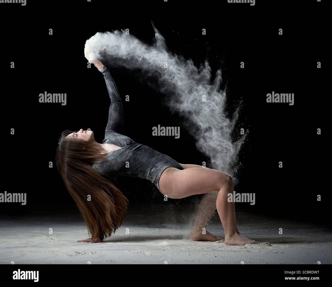 Junge schöne Frau mit langen Haaren ist in einem Sport schwarzen Body gekleidet und sitzt auf dem Boden und wirft weißes Mehl über ihren schwarzen Hintergrund Stockfoto