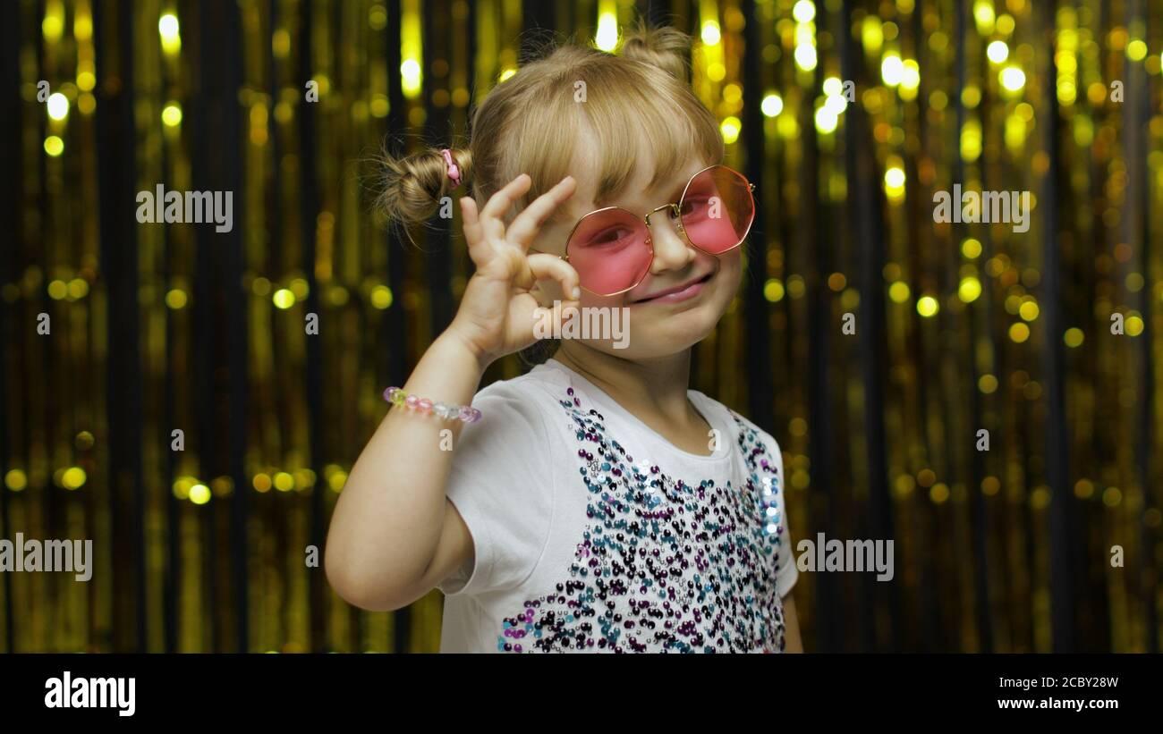 Fröhlich froh Kind zeigt ok Geste und lächelt an der Kamera mit optimistischen zufriedenen Ausdruck, okay Zeichen der Zustimmung. Wenig Spaß blonde Kind Teenager Mädchen 4-5 Jahre alt in rosa Sonnenbrille Stockfoto