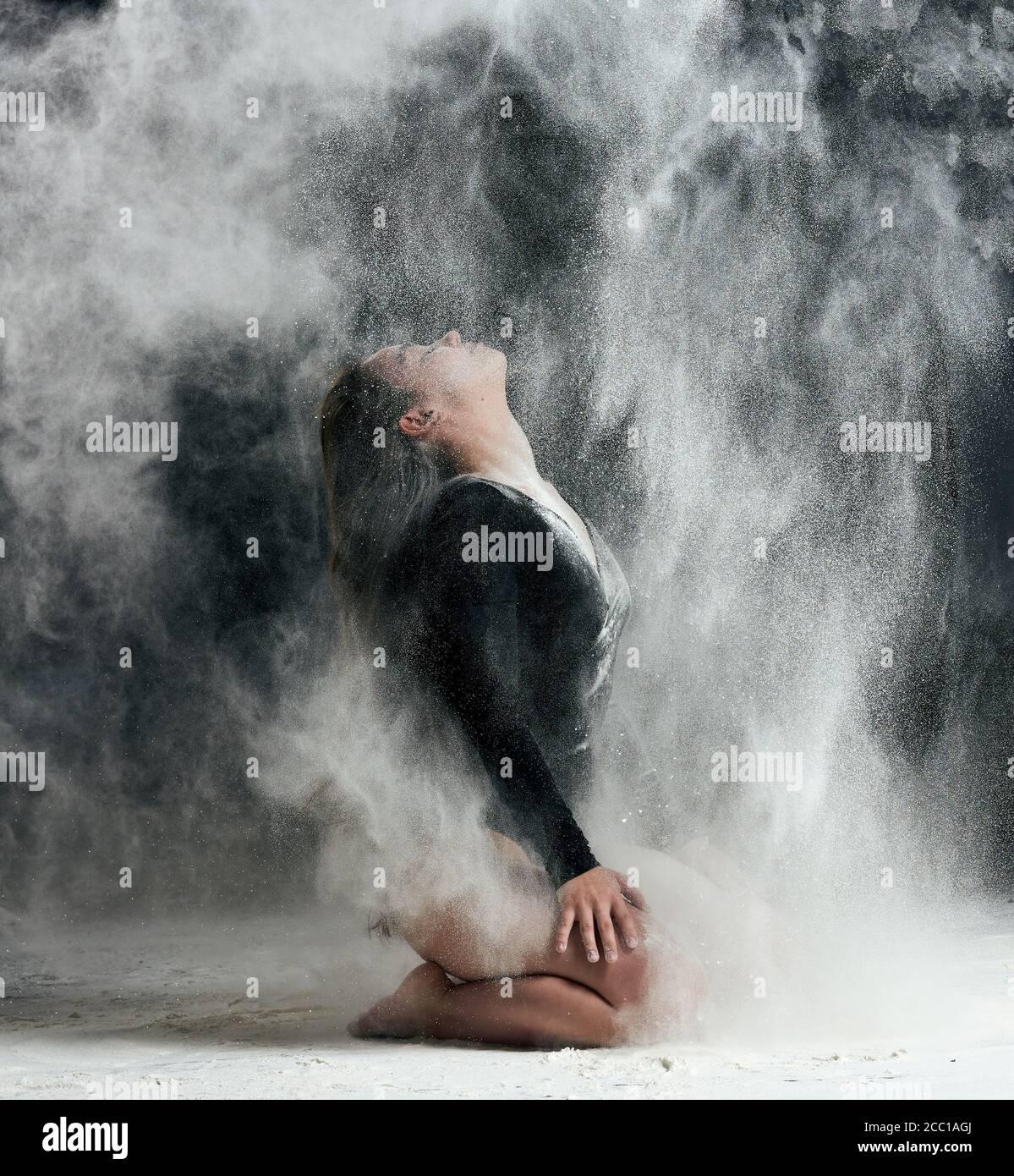 Junge schöne kaukasische Frau mit langen Haaren ist in einem Sport schwarzen Body gekleidet und sitzt auf dem Boden und wirft weißes Mehl, schwarze Backgrou Stockfoto