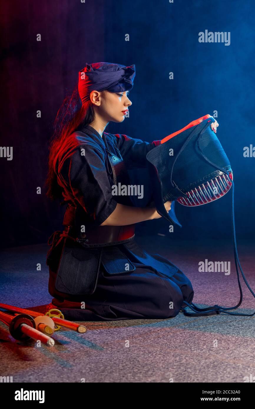 kaukasischen Kendo Kämpfer sitzen auf dem Boden vor dem Kampf, tragen spezielle Kendo Kleid und mit allen Geräten, Bambus Schwert Shinai. japanische Martial A Stockfoto