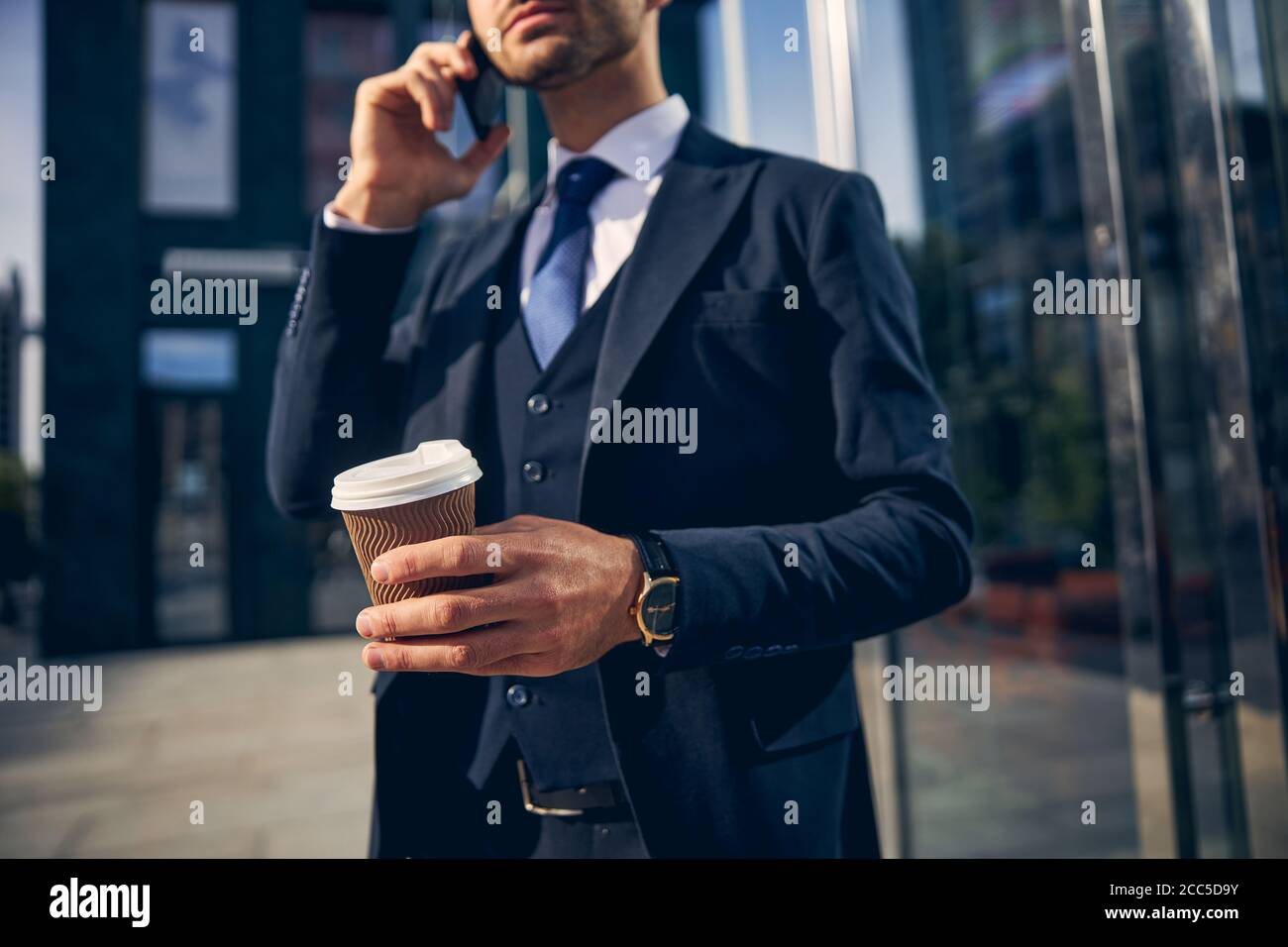 Junger Mann, der vor dem Büro telefoniert Stockfoto