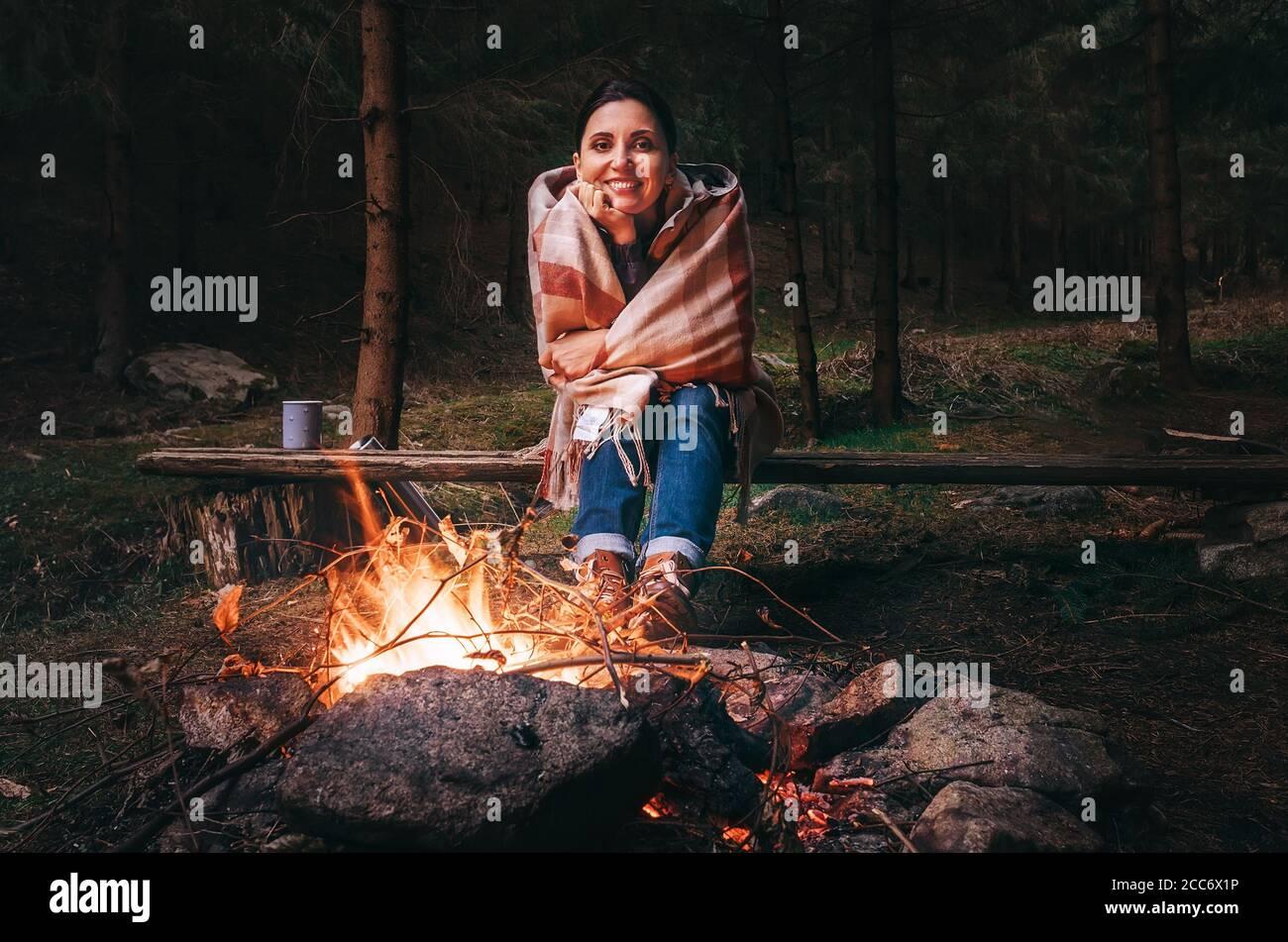 Hübsche lächelnde junge Frau sitzt in der Dämmerung am Lagerfeuer Herbstwald Stockfoto