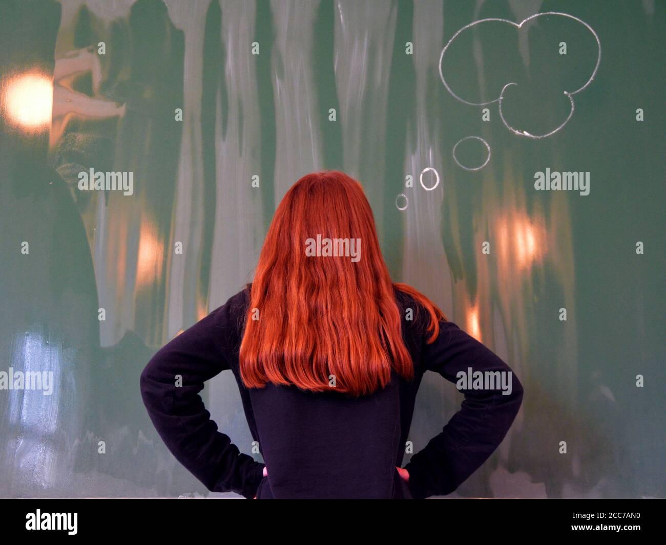 Redhead Schulmädchen steht vor dem Brett und Denken...Konzept Zum Hinzufügen von Text Stockfoto