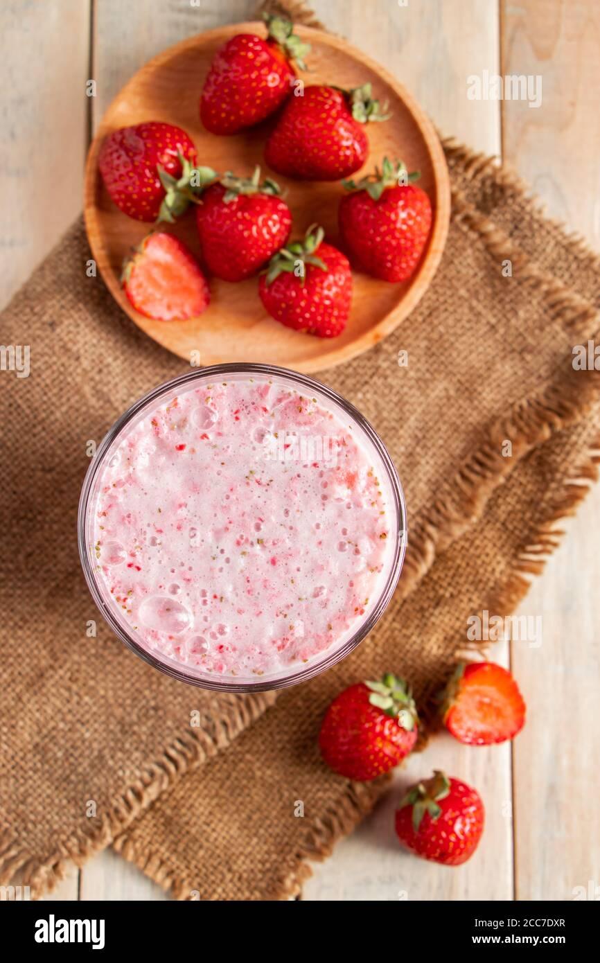 Frischer Milchshake mit Erdbeeren. Sommergetränk mit Beeren in einem Glas auf einem Holzhintergrund. Vertikales Foto Stockfoto