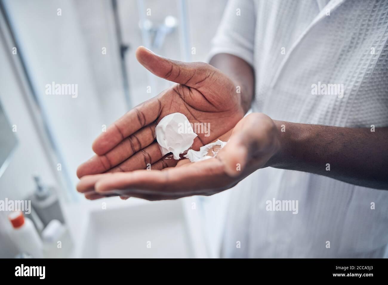 Nahaufnahme der männlichen Hände, die Schaum halten Stockfoto