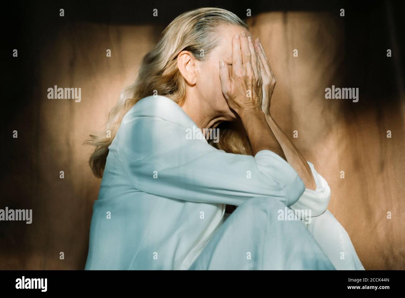 Traurige ältere Frau, die allein sitzt und das Gesicht mit den Händen bedeckt Stockfoto