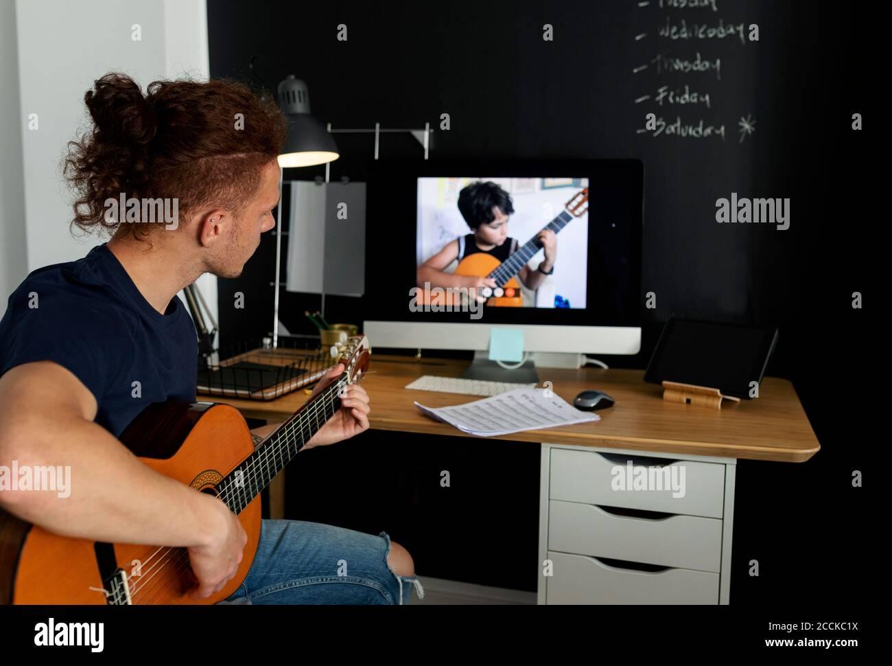 Mann, der Gitarre lernt, während er Tutorial zu Hause ansieht Stockfoto