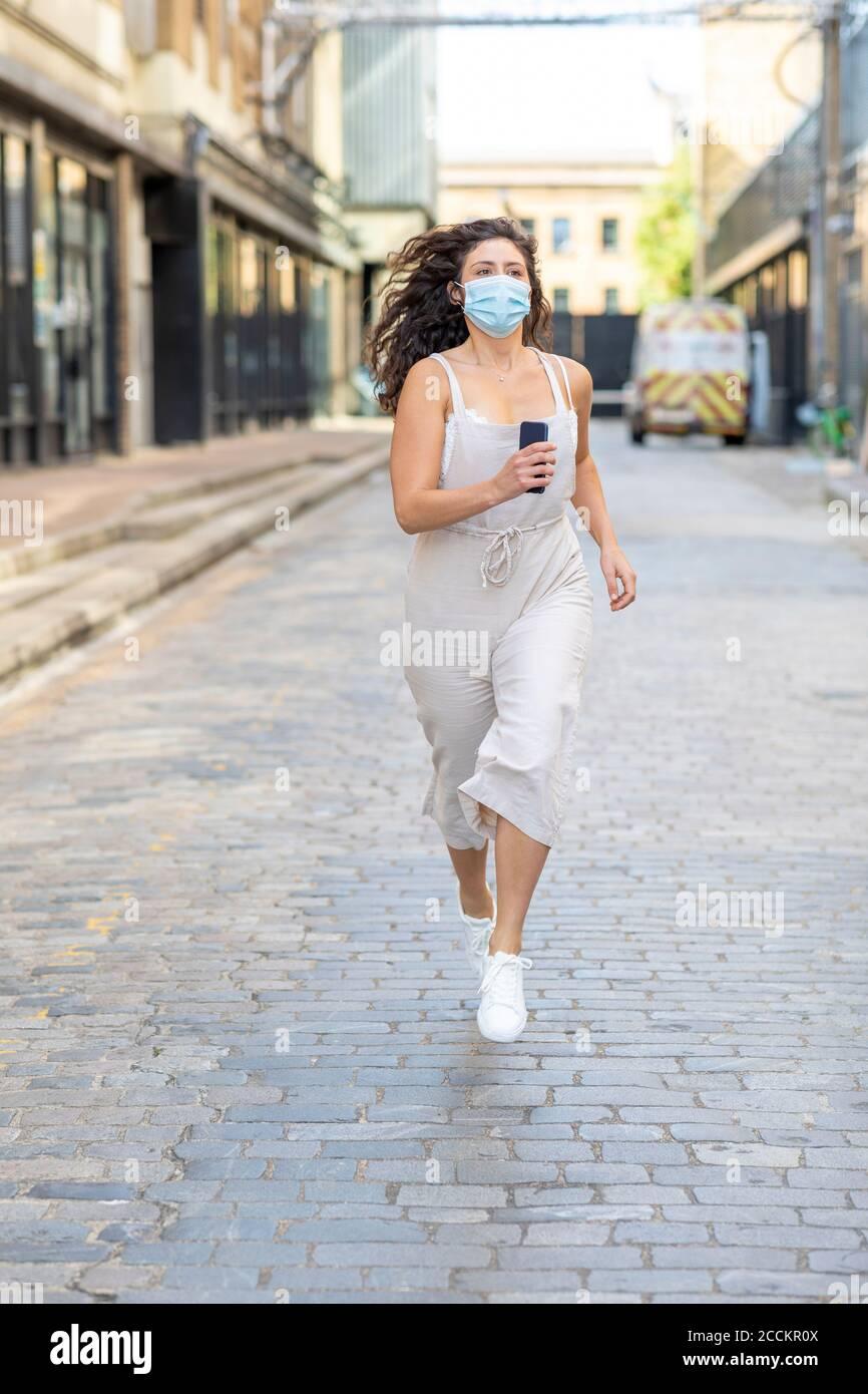 Junge Frau trägt Maske läuft auf der Straße in der Stadt Stockfoto