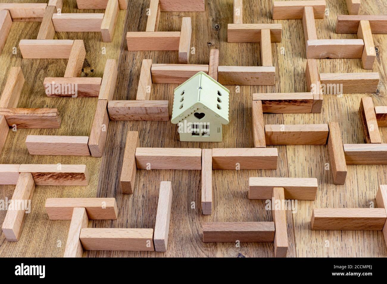 Immobilienkonzept, Holzmaze Modell mit Haus in der Mitte Stockfoto