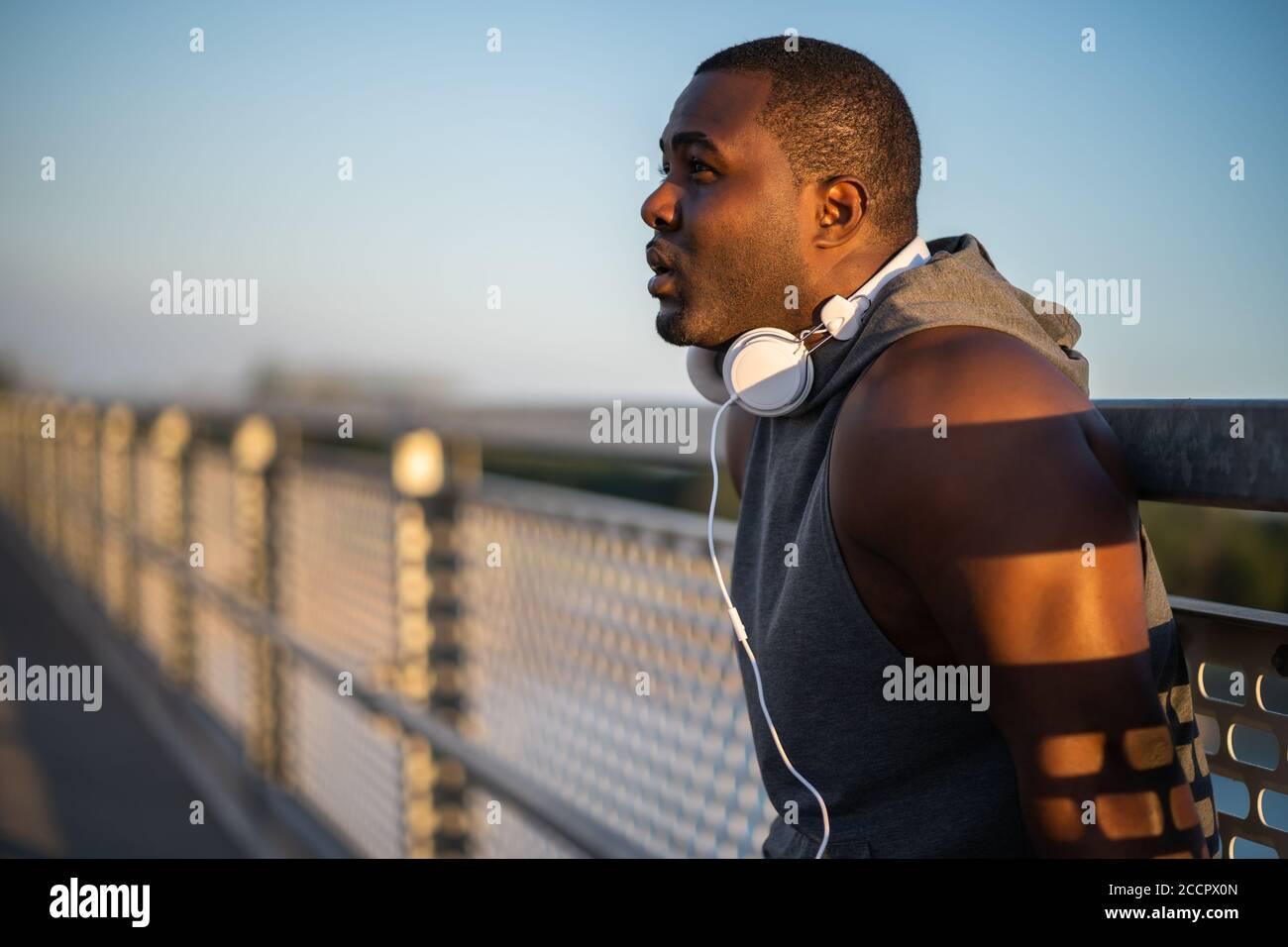 Porträt eines jungen fröhlichen afroamerikanischen Mannes in Sportkleidung, der sich nach dem Joggen entspannt. Stockfoto