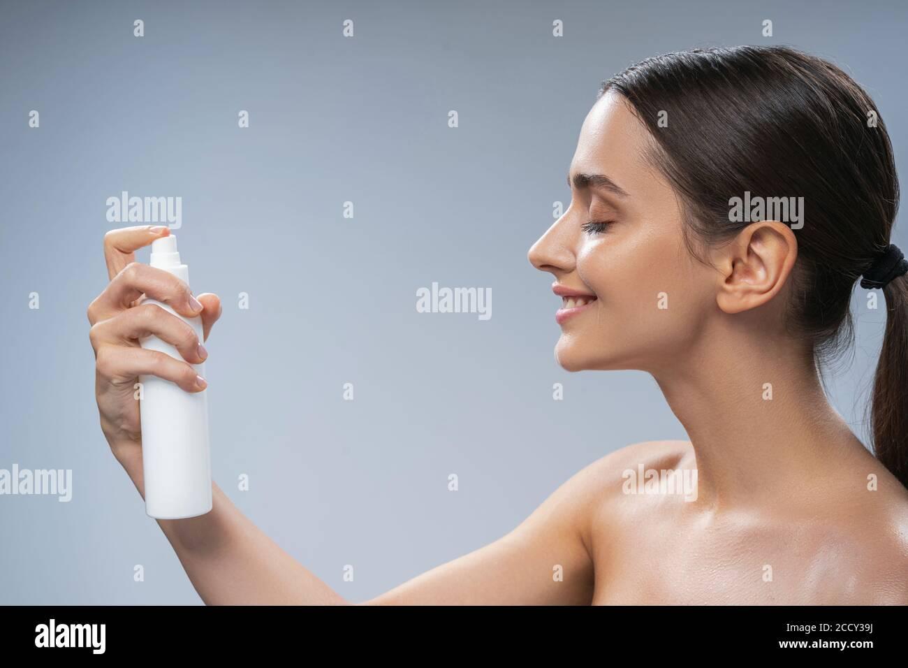 Frau sprüht Thermalwasser auf ihre Haut Stockfoto