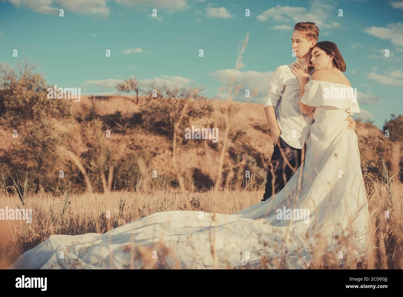 Junge Hochzeit Paar von einem Mann und einem Mädchen, in einem weißen Kleid, auf einem Feld, vor dem Hintergrund eines bewölkten blauen Himmel, Sonnenuntergang. Liebe zum jungen Peop Stockfoto