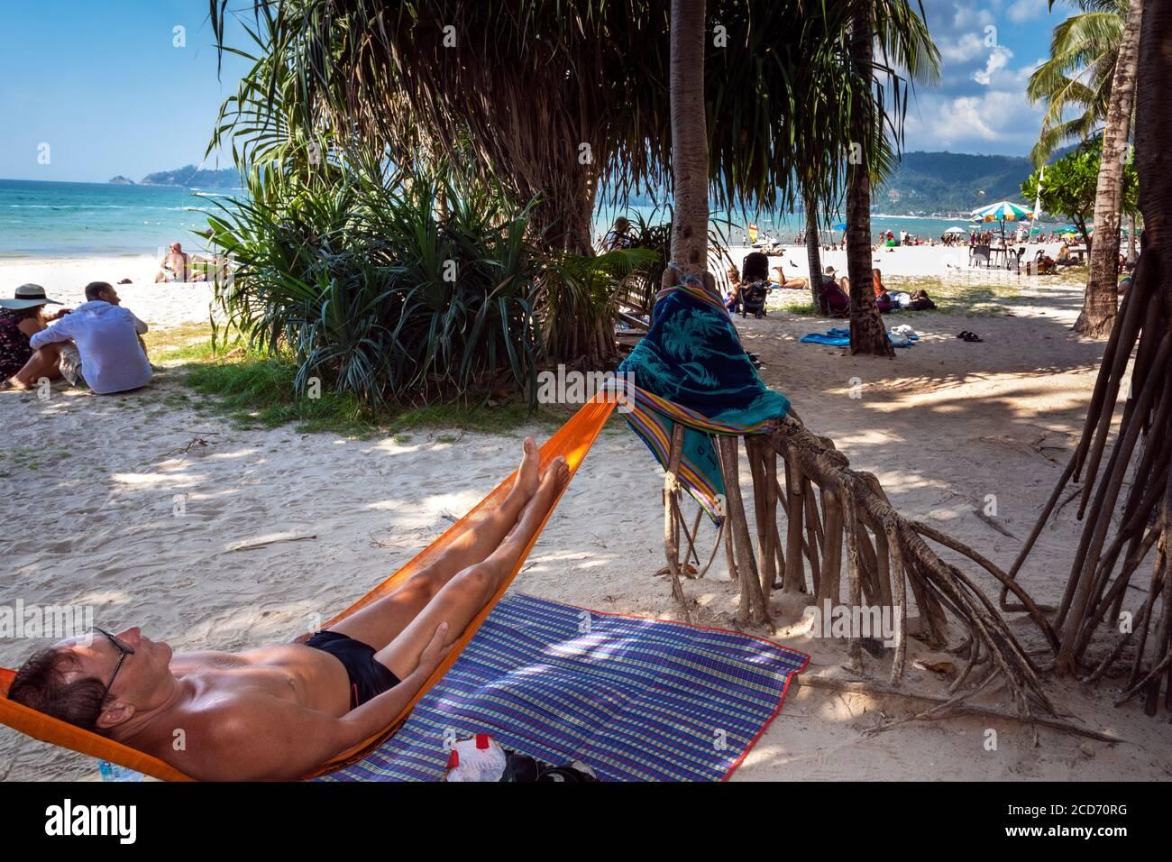 Tourist relaxen in einer Hängematte am Strand von Patong, Phuket, Thailand Stockfoto