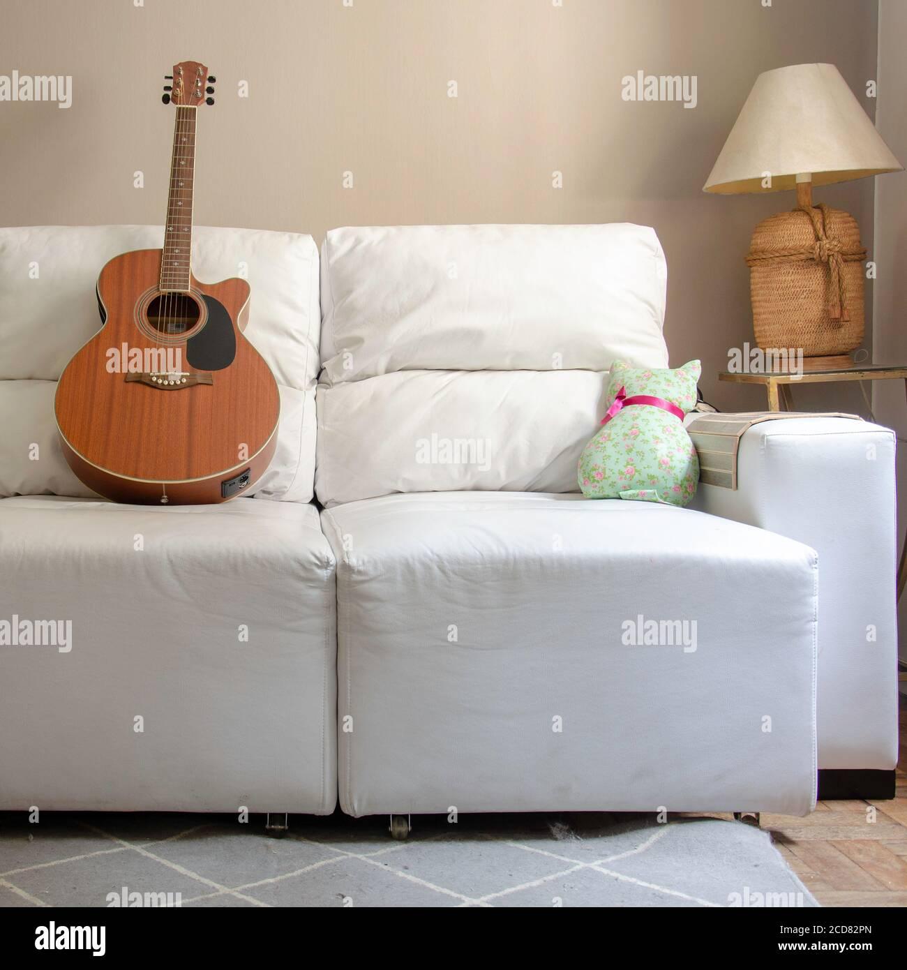 Wohnkultur: Wohnzimmer mit Holzgitarre über einem weißen Sofa und Lampe auf Beistelltisch mit hellbrauner Hintergrundwand Stockfoto
