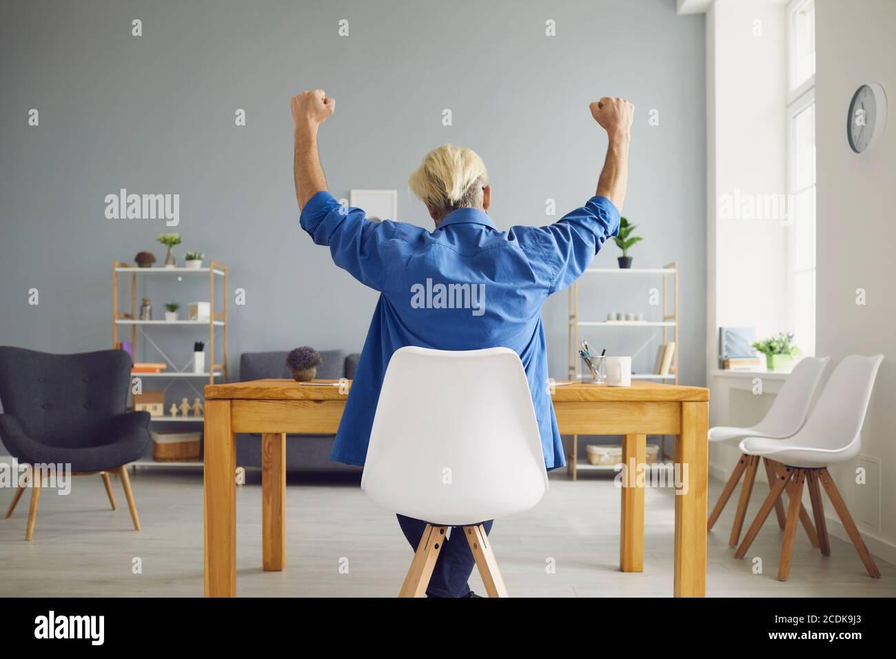 Nicht erkennbarer Hipster sitzt am Tisch und zeigt ja Geste Stockfoto